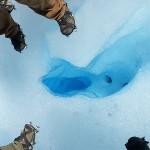 Steigeisen um ein blaues Eisloch